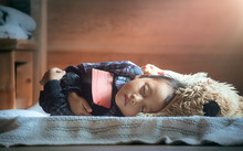 Cute Little Girl Happily Embracing A Bible And Fell Asleep. Christian Concept.