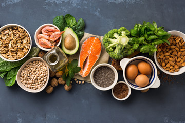 Health food fitness. Food sources of omega 3 on dark background top view. Foods high in fatty acids including vegetables, seafood, nut and seeds