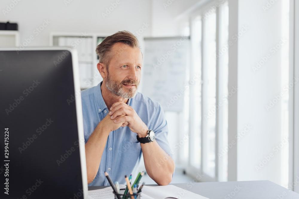Fototapeta Thoughtful businessman staring through a window
