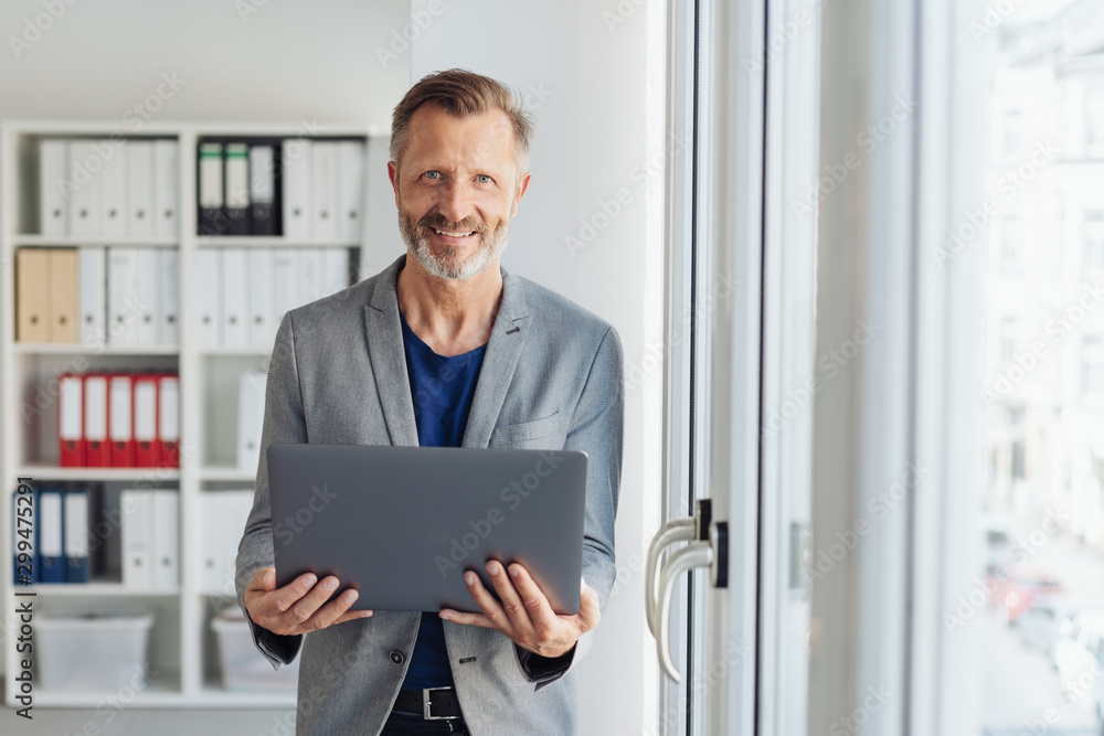 Fototapety, obrazy: Smiling professional man holding an open laptop