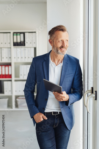 Smart businessman standing waiting with a tablet