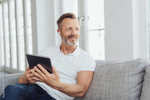 Middle-aged man listening to music on an ear bud Wallpaper Mural