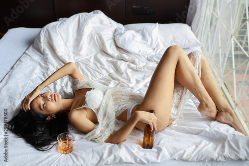 high angle view drunken asian woman in white lingerie, drinking and holding bott Canvas-taulu