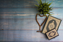 Flat Lay View Of Vase, Tasbih Or Rosary Beads And Holy Book Of Quran With Arabic Calligraphy Meaning Of Al Quran Over Wooden Paper Background. Selective Focus And Crop Fragment