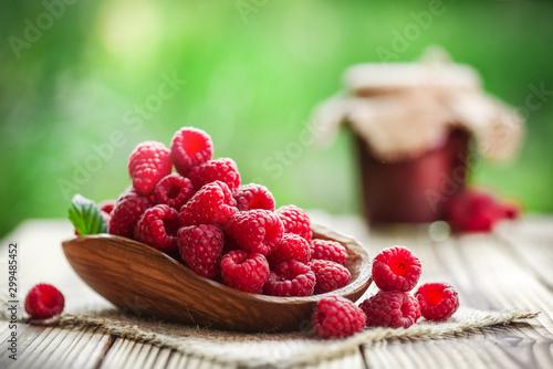 Fototapeta Fresh forest raspberries in wooden basket on rustic table. Sweet raspberry jam in background. obraz na płótnie