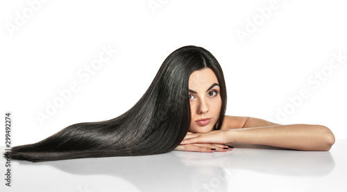 Photographie Portrait of beautiful young woman with healthy long hair on white background