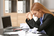 Stressed woman at workplace in office