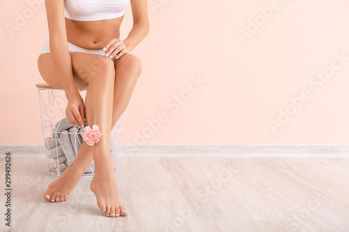 Obraz Woman with beautiful legs after depilation near color wall - fototapety do salonu
