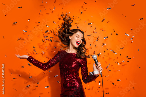 Portrait of positive cheerful girl enjoy bachelor party celebration sing song in karaoke hold microphone wear burgundy red clothes isolated over orange color background confetti hair flying falling - 299492863