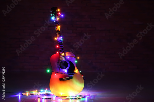 Photo Acoustic guitar with Christmas lights against dark background
