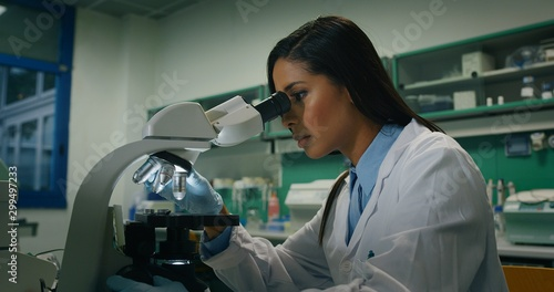 Fotografía  Close up of dark skin female scientist is analyzing a sample to extract the DNA and molecules with microscope in laboratory