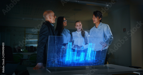 A group of modern designers are using a futuristic sophisticated technology screen with augmented reality holograms for a new project realization in an office Canvas Print