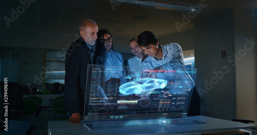 Photo A group of modern engineers are designing an electric car by using futuristic sophisticated technology screen with augmented reality holograms in a creative studio