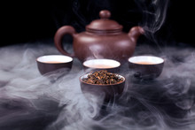 Asian Tea Ceremony. Clay Teapot And Tea Cups With Vapor On A Black Background.