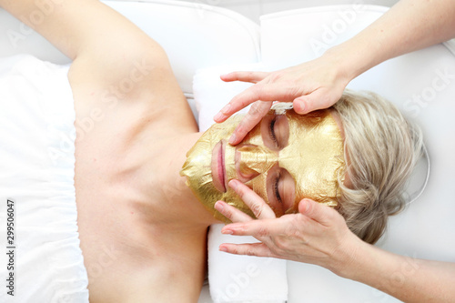 Gold cosmetic mask, the beautician applies a gold mask to a woman's face. The beautician applies a golden mask to a woman's face. Beautiful woman in a beauty salon during facial treatment