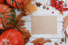 Orange Pumpkins, Yellow Oak Leaves, Spices, Acorns, Red Berries, Blank Paper For Text On White Wooden Table. Welcome Autumn, Harvest Festival, Halloween, Thanksgiving Concept. Top View, Copy Space