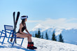 Skier girl in black swimsuit and helmet, sitting at a bench near skis and enjoing wonderfull view at the mountains on ski resort. Blue sky, forests, mountains on the background. Ski season concept