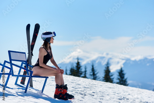 Fotografía  Skier girl in black swimsuit and helmet, sitting at a bench near skis and enjoing wonderfull view at the mountains on ski resort