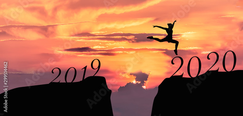 Foto auf Gartenposter Koralle Happy new year 2020, Silhouette of 2020 letters on the mountain with business people jump across gap of mountain at sunrise.