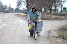 Man Pushing His Laden Bicycle Along A Quiet Street