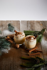 eggnog cocktail with whipped cream and cinnamon near spruce branches and powdered sugar scattered on wooden table isolated on grey