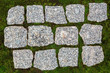 Granite paving stones on a green field