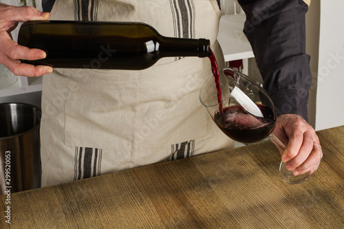 Hombre con botella de vino en la mano sirviendo el vino en una copa Fototapete