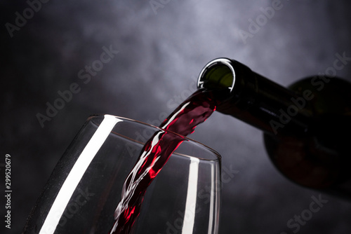 Foto auf Leinwand Alkohol red wine pouring into glass