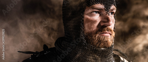 Fotografija panoramic shot of handsome knight in armor looking away on black background
