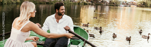 panoramic shot of young couple in boat on lake near flock of ducks Fototapeta