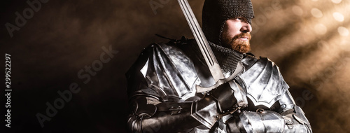 panoramic shot of handsome knight in armor holding sword on black background Fototapet