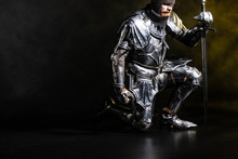 Handsome Knight In Armor Holding Sword And Bend Knee On Black Background