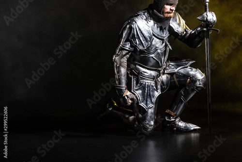 handsome knight in armor holding sword and bend knee on black background Tableau sur Toile