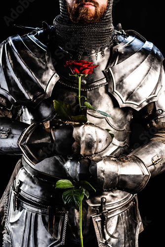 cropped view of knight in armor holding rose isolated on black