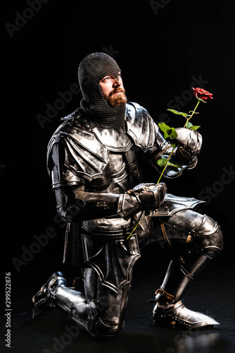 handsome knight in armor holding rose and bend knee on black background