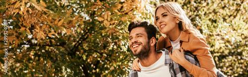 Obraz panoramic shot of cheerful man piggybacking happy girlfriend in park - fototapety do salonu