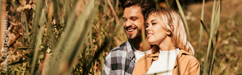 Obraz na plátně  selective focus of happy young couple smiling in thicket of sedge, panoramic sho