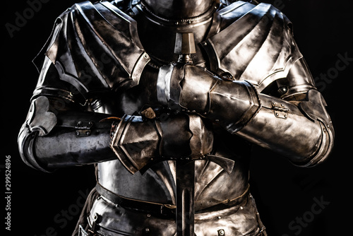 Photo cropped view of knight in armor holding sword isolated on black