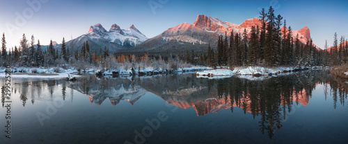 Fototapeta Almost nearly perfect reflection of the Three Sisters Peaks in the Bow River. Near Canmore, Alberta Canada. Winter season is coming. Bear country. Beautiful landscape background concept. obraz