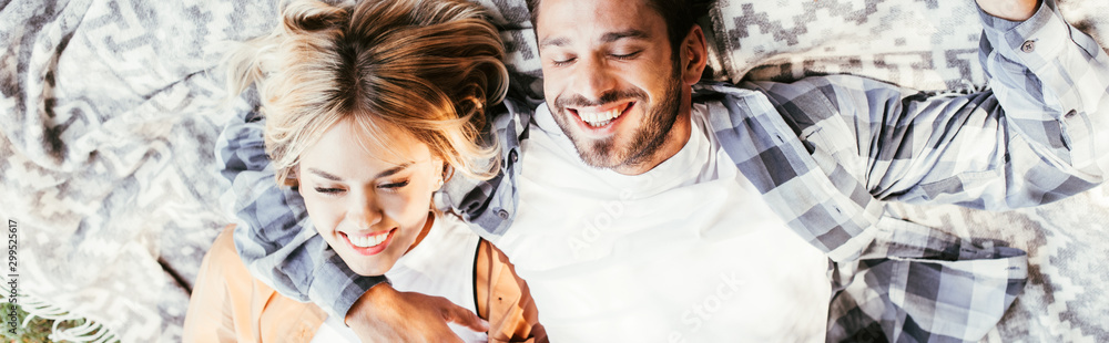 Fototapety, obrazy: top view of cheerful man embracing happy girlfriend while lying on blanket in park, panoramic shot