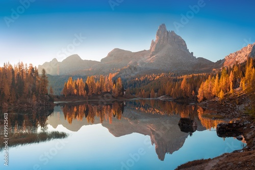 Foto op Plexiglas Herfst Autumn view of Lake Federa in Dolomites at sunset. Fantastic autumn scene with blue sky, majestic rocky mount and colorful trees glowing sunlight in Dolomites. Dolomite Alps with yellow larch trees