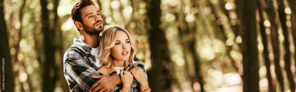 Fototapeta panoramic shot of happy man embracing attractive girlfriend while looking away in park