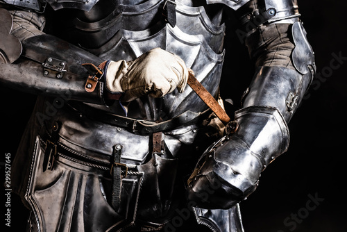 Foto op Canvas Paarden cropped view of knight in armor holding sword isolated on black