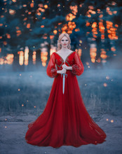Beautiful, Dangerous Blonde Queen In A Red Fashion Lush Dress With A Dagger In Her Hands. Backdrop Dark Fantasy Forest In A Fog. Fiery Sunset. Concept Revenge, Conspiracy And Betrayal. Halloween Party
