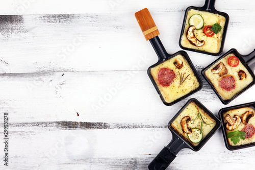 Fotografia Delicious traditional Swiss melted raclette cheese on diced boiled or baked potato