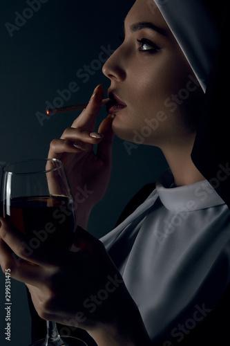 Vászonkép Close-up profile portrait of a nun, posing on a black background