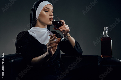 Cropped half-turn shot of a nun, sitting on a chair Canvas Print