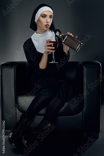 Photo Full length shot of a nun, sitting on a chair
