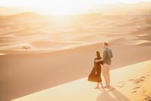 Loving Couple In Sahara Desert.