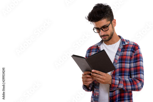 Fotomural  Portrait of young bearded Persian hipster man reading book